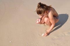 Muchacha que recoge shelles en la playa Fotografía de archivo libre de regalías