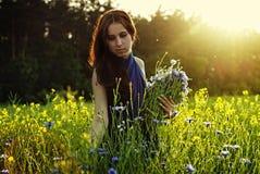Muchacha que recolecta las flores en puesta del sol Imagen de archivo