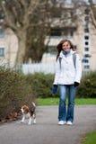 Muchacha que recorre con un perro Imagen de archivo libre de regalías