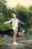 Muchacha que recorre en la lluvia Imagenes de archivo