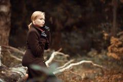 Muchacha que recorre en parque del otoño El sentarse en un árbol Muchacha en la madera Fotos de archivo