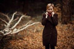 Muchacha que recorre en parque del otoño El sentarse en un árbol Muchacha en la madera foto de archivo
