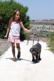 Muchacha que recorre su perro Foto de archivo libre de regalías