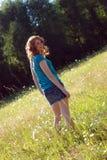 Muchacha que recorre a través del campo de la hierba - vertical Foto de archivo