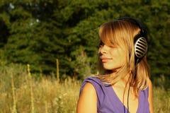 Muchacha que recorre y que escucha la música al aire libre Foto de archivo
