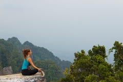Muchacha que reflexiona sobre el top de la montaña fotografía de archivo libre de regalías