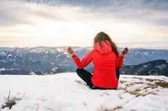 Muchacha que reflexiona sobre el top nevado de la montaña Fotografía de archivo libre de regalías