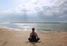 Muchacha que reflexiona sobre la playa en el sol imagen de archivo