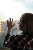 Muchacha que retrocede en el balcón con la mano sobre el vidrio Imagenes de archivo