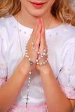 Muchacha que ruega en el día de la primera comunión santa Imágenes de archivo libres de regalías