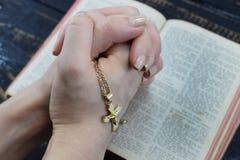 Muchacha que ruega sobre la Sagrada Biblia que se sostiene en su cruz de la mano Foto de archivo libre de regalías