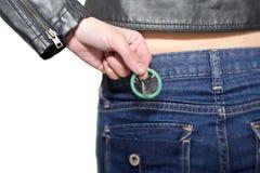 Muchacha que saca los preservativos de su bolsillo de la mezclilla Fotografía de archivo