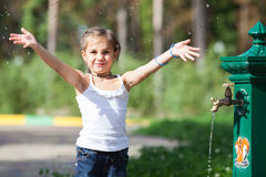 Muchacha que salpica el agua en el parque Imagenes de archivo