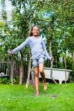 Muchacha que salta en el jardín imagen de archivo libre de regalías