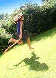 Muchacha que salta en jardín Foto de archivo