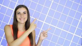 Muchacha que señala con el finger en el lado, fondo azul almacen de video
