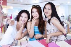 Muchacha que señala en la tienda con sus amigos Fotos de archivo