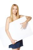 Muchacha que señala en un tablero en blanco Foto de archivo