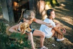 Muchacha que señala y que abraza su perro en un patio Imágenes de archivo libres de regalías