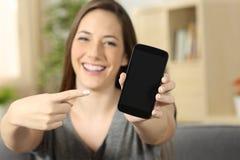 Muchacha que señala y que muestra una pantalla en blanco del teléfono Fotografía de archivo