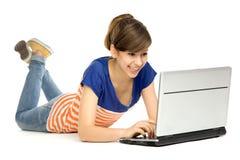 Muchacha que se acuesta con la computadora portátil Fotografía de archivo libre de regalías