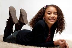 Muchacha que se acuesta con una sonrisa grande Foto de archivo libre de regalías