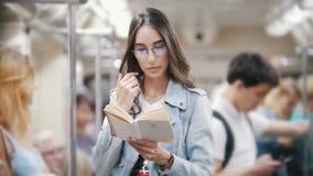 Muchacha que se aferra a la barandilla y que lee un libro en el metro, cámara lenta metrajes
