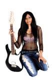 Muchacha que se arrodilla con una guitarra. Fotos de archivo