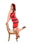 Muchacha que se arrodilla en silla. Fotos de archivo