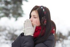 Muchacha que se calienta las manos en invierno Fotos de archivo libres de regalías