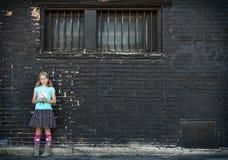 Muchacha que se coloca al lado de la pared de ladrillo Fotografía de archivo