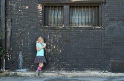 Muchacha que se coloca al lado de la pared de ladrillo Imagenes de archivo