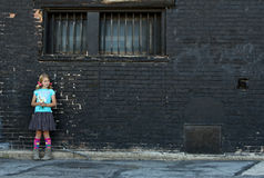 Muchacha que se coloca al lado de la pared de ladrillo Fotografía de archivo libre de regalías