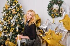 Muchacha que se coloca al lado de un árbol de navidad y de presentes Fotos de archivo