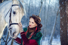 Muchacha que se coloca al lado de un caballo blanco fotos de archivo