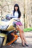 Muchacha que se coloca al lado de una motocicleta Foto de archivo