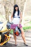 Muchacha que se coloca al lado de una motocicleta Imágenes de archivo libres de regalías