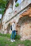 Muchacha que se coloca cerca de la pared destruida en un parque Imagen de archivo libre de regalías