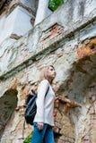 Muchacha que se coloca cerca de la pared destruida en un parque Imágenes de archivo libres de regalías