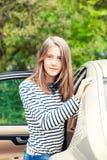 Muchacha que se coloca cerca del coche que mira la cámara Verano hacia fuera Fotografía de archivo