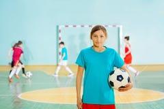 Muchacha que se coloca con el balón de fútbol en gimnasio de la escuela Imagen de archivo libre de regalías
