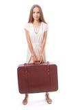 Muchacha que se coloca con la maleta Aislado en blanco Fotografía de archivo