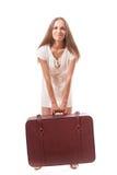 Muchacha que se coloca con la maleta Aislado en blanco Imágenes de archivo libres de regalías