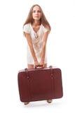 Muchacha que se coloca con la maleta Aislado en blanco Imagen de archivo