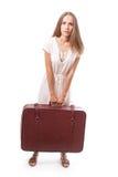 Muchacha que se coloca con la maleta Aislado en blanco Foto de archivo