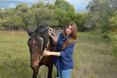 Muchacha que se coloca con un caballo Foto de archivo