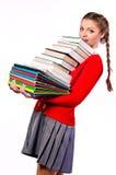 Muchacha que se coloca con un manojo de libros Imagenes de archivo