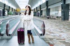 Muchacha que se coloca con una maleta en el pasillo del aeropuerto Foto de archivo