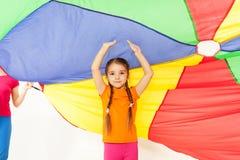 Muchacha que se coloca debajo del toldo de paracaídas parti-coloreado Fotografía de archivo libre de regalías