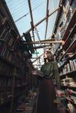 Muchacha que se coloca en biblioteca con los libros Fotografía de archivo libre de regalías